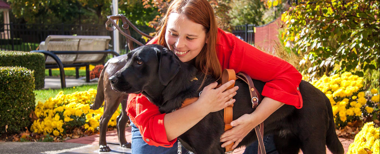 A female handler hugs her black Lab guide dog.