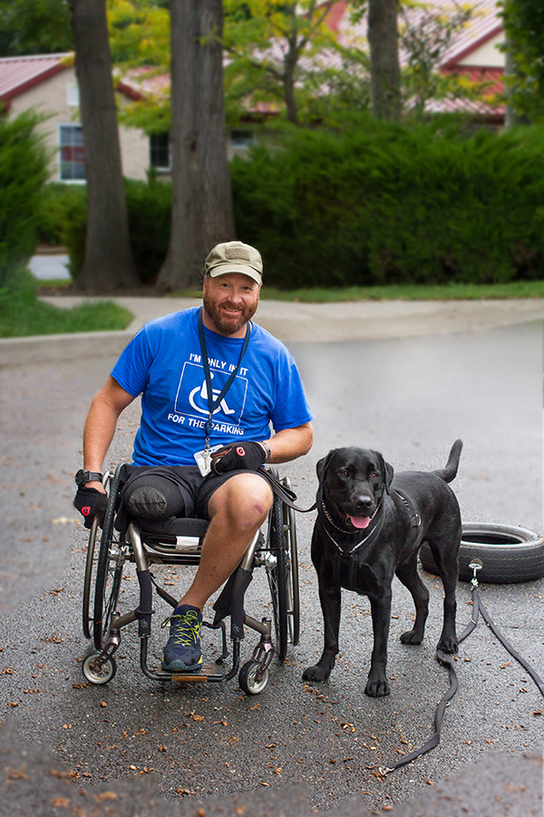 A veteran and his black lab service dog.