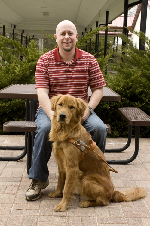 Brian and his guide dog pose for a portrait.