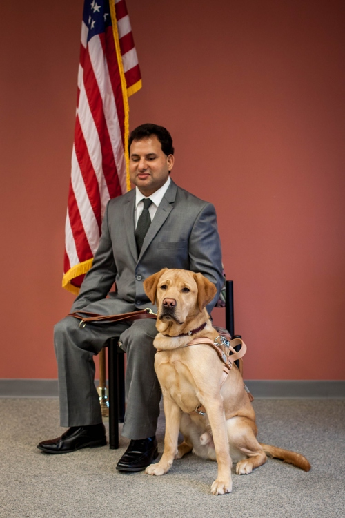 Portrait of Hari and his guide dog sitting next to him.