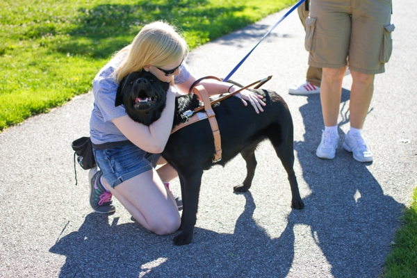 A woman hugs her new black Lab guide dog.