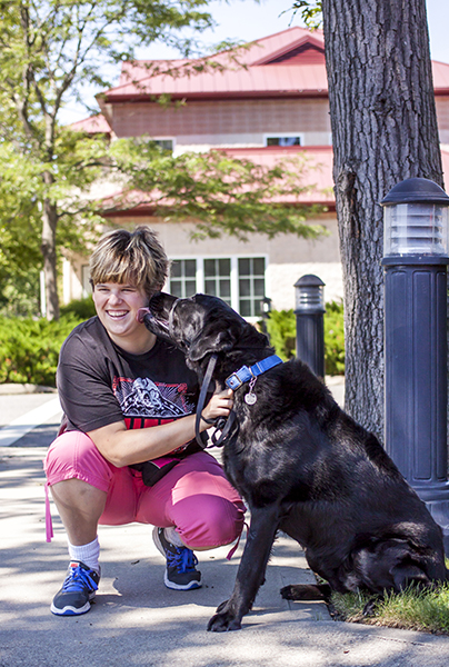 A volunteer gets a kiss from a black Lab she's taking out for a walk.