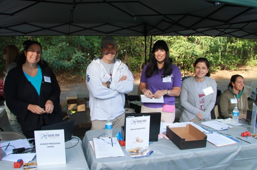 A group of volunteers work at an event registration table.