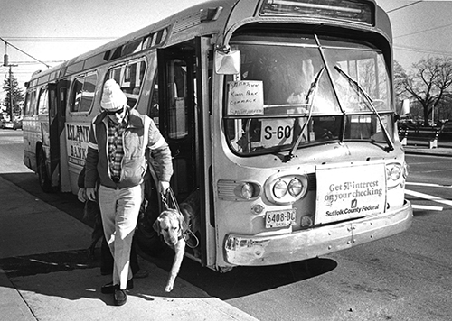 guide dog team exits a bus. 1980s