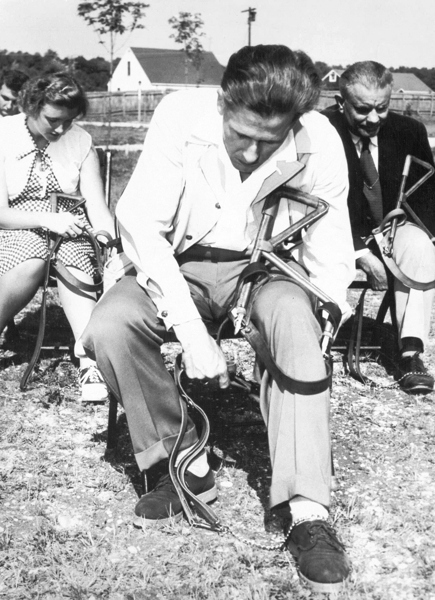 A group of students practice working with their harness on their knee.