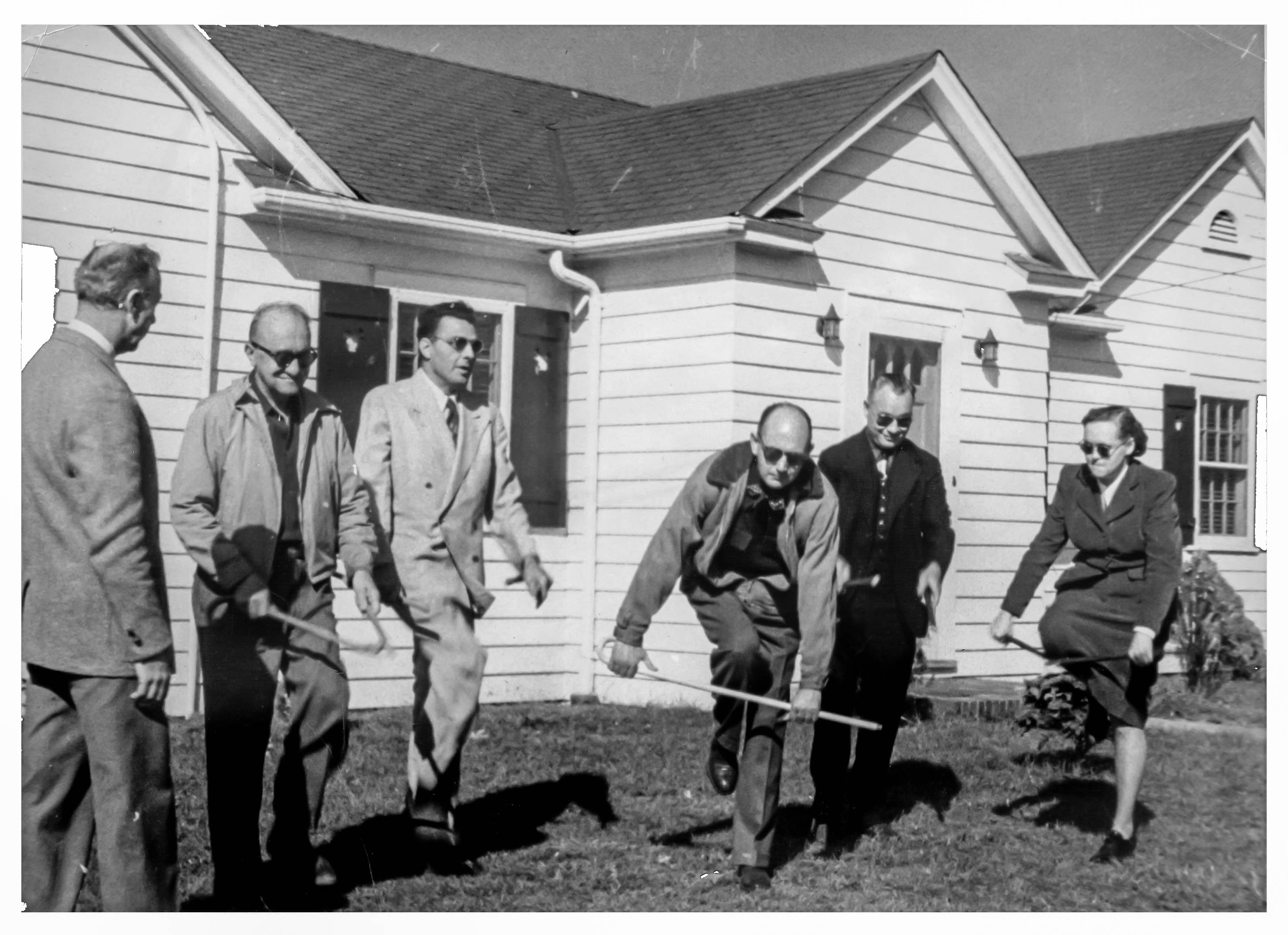 A group of guide dog students stand in front of the original dormitory as they break their canes over their knees.