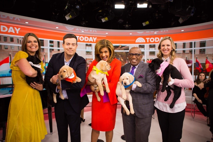 The TODAY cast each holding a pup.
